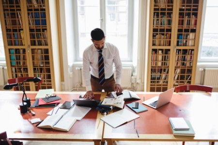 man researching while standing at table in home library