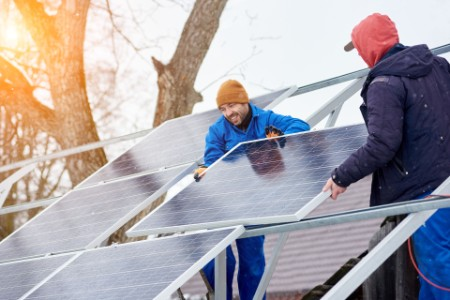 ey technicians mounting blue solar modules on roof