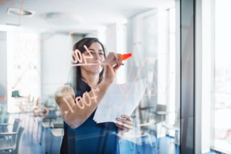 Business woman writing on glass wall