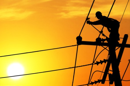 Shadow electricians repairing wire on electric power pole at the sunset blur