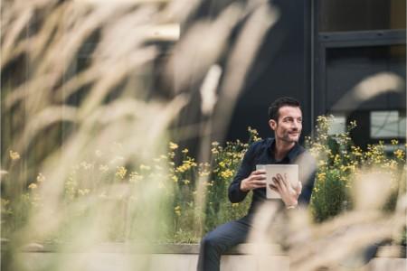 Mann sitzt mit Kaffee draußen