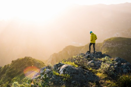 Mann steht auf einem Berg
