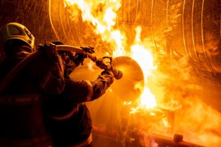 Der Feuerwehrmann löscht das Feuer.