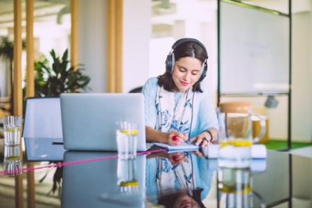 Frau sitzt mit Kopfhörern vor dem Laptop und macht Notizen