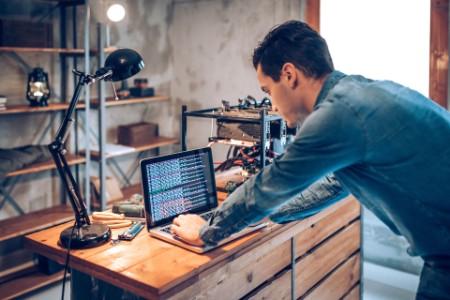 Mann am Schreibtisch vor mehreren Monitoren