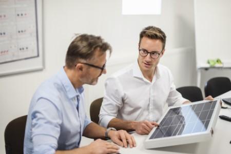 Zwei Kollegen schauen sich ein Photovoltaik Panel an