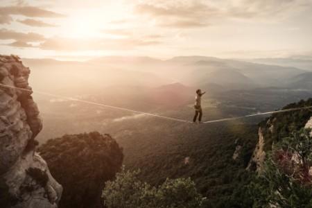 Mann balanciert auf Seil im Gebirge