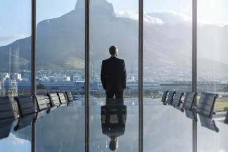 Mann im Anzug steht in leerem Konferenzraum durch großes Fenster nach draußen blickend da