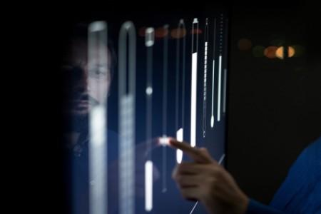 Mann, der im Kontrollraum arbeitet und Schieberegler auf dem Bildschirm bewegt