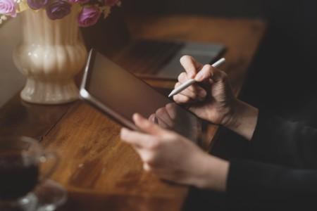 Frau schreibt auf einem Tablet