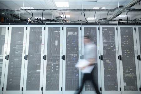 Mann läuft durch einen Serverraum