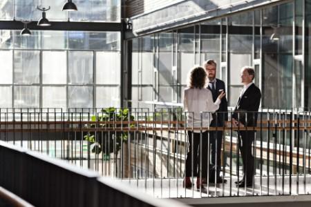 Drei Personen unterhalten sich in einem Bürogebäude