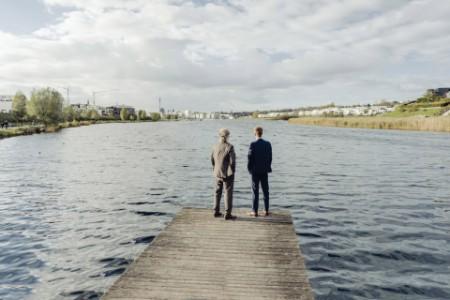 Zwei Geschäftsleute stehen auf einem Steg an einem See