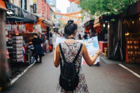 Frau mit Stadtkarte läuft durch eine Straße mit Ständen