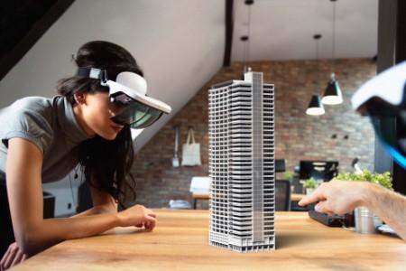 Zwei Personen arbeiten an einem virtuellen 3D-Gebäude mit einer AR-Brille
