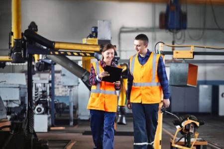 Männliche und weibliche Industriearbeiter verwenden ein Tablet und gehen durch eine Schwerindustrie-Fabrik