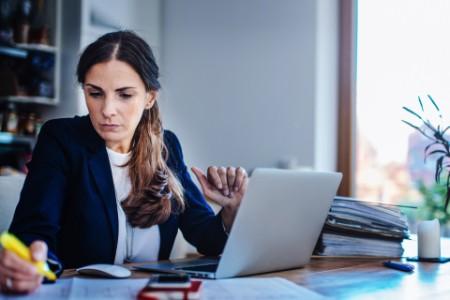 Frau am Schreibtisch vor Laptop mit Textmarker