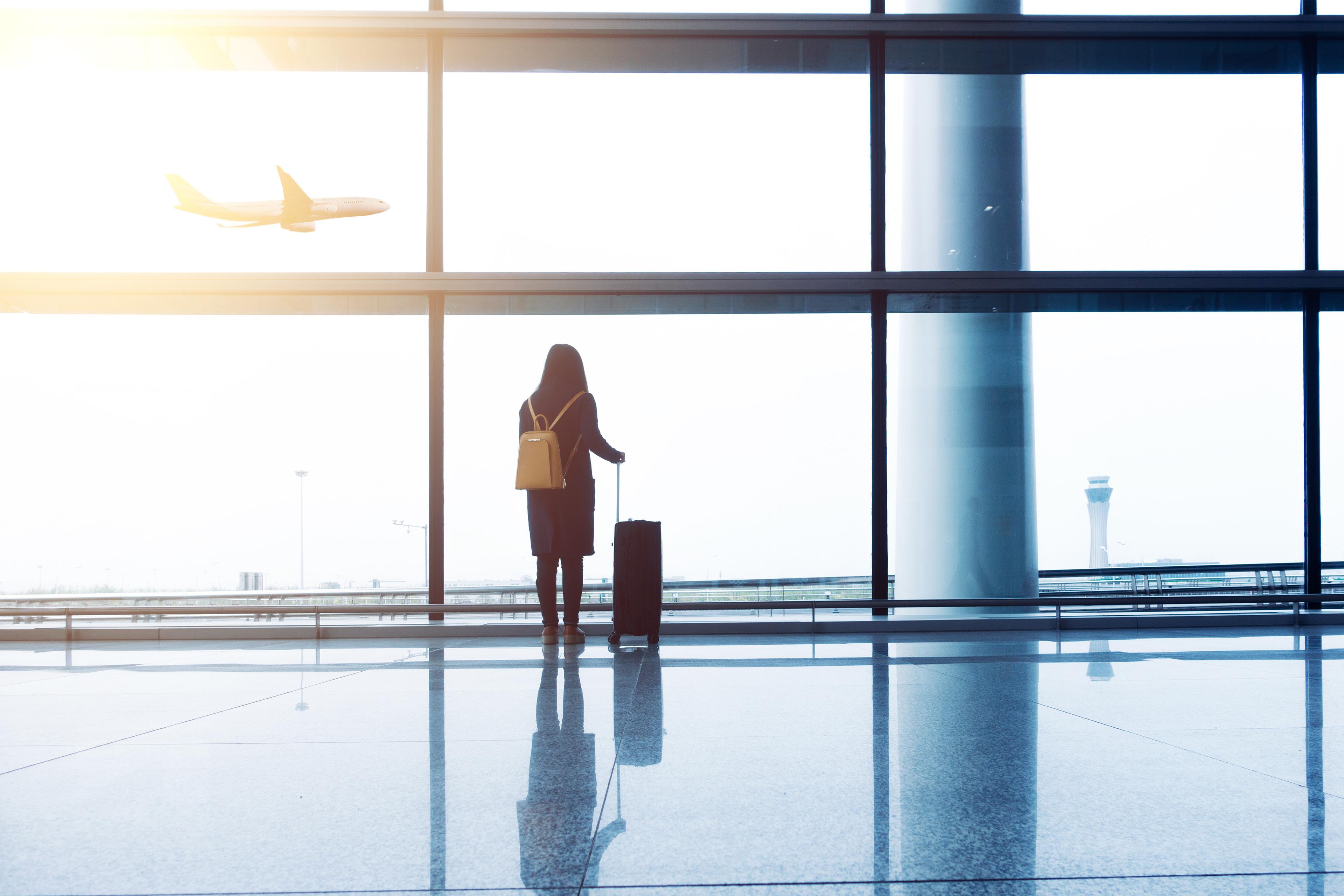 Praktikantenförderprogramm Xperience von EY: Frau mit Koffer in Flughafenhallte beobacht Flieger.