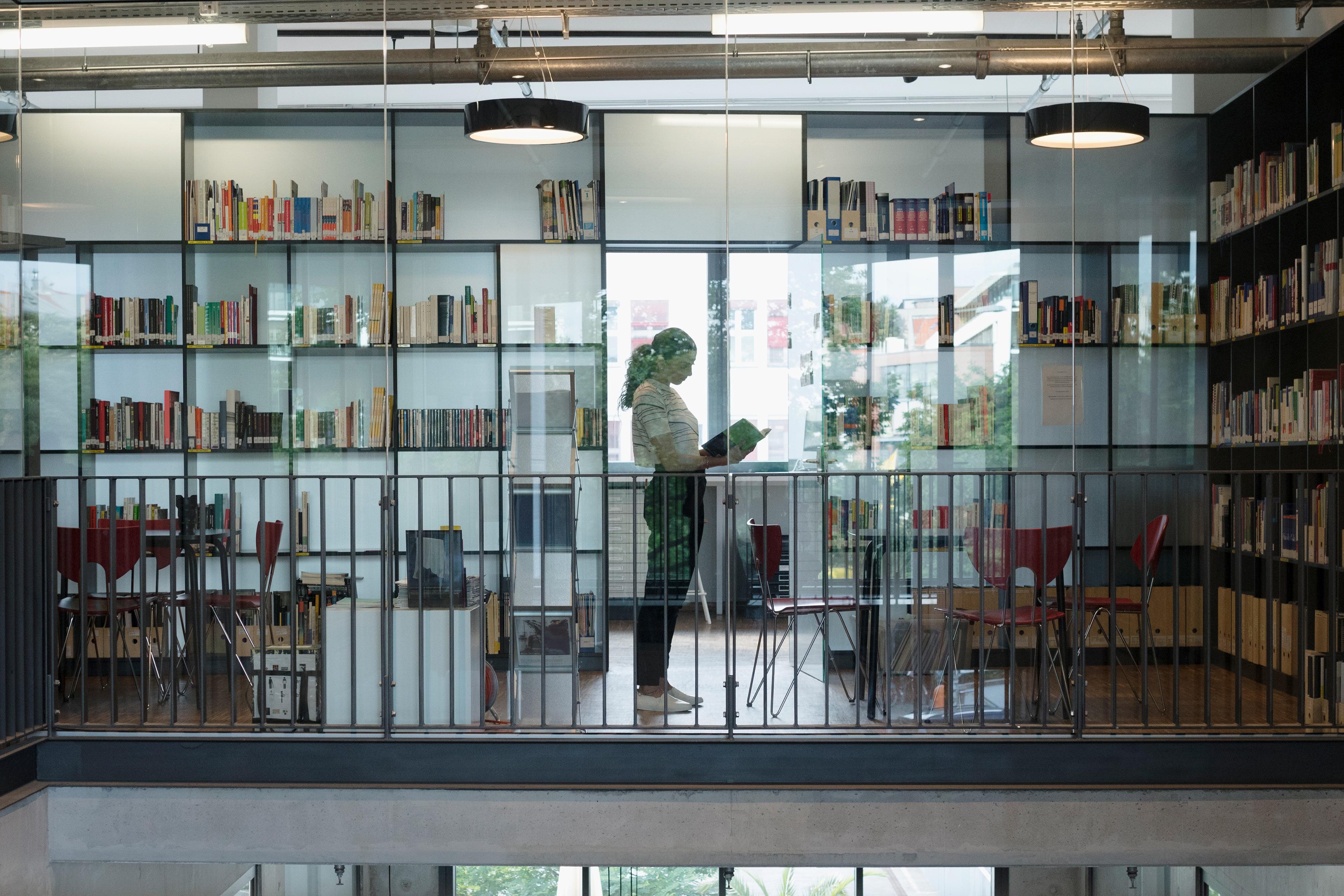 Frau in Bibliotheksraum – Fragen und Antworten zur Bewerbung bei EY