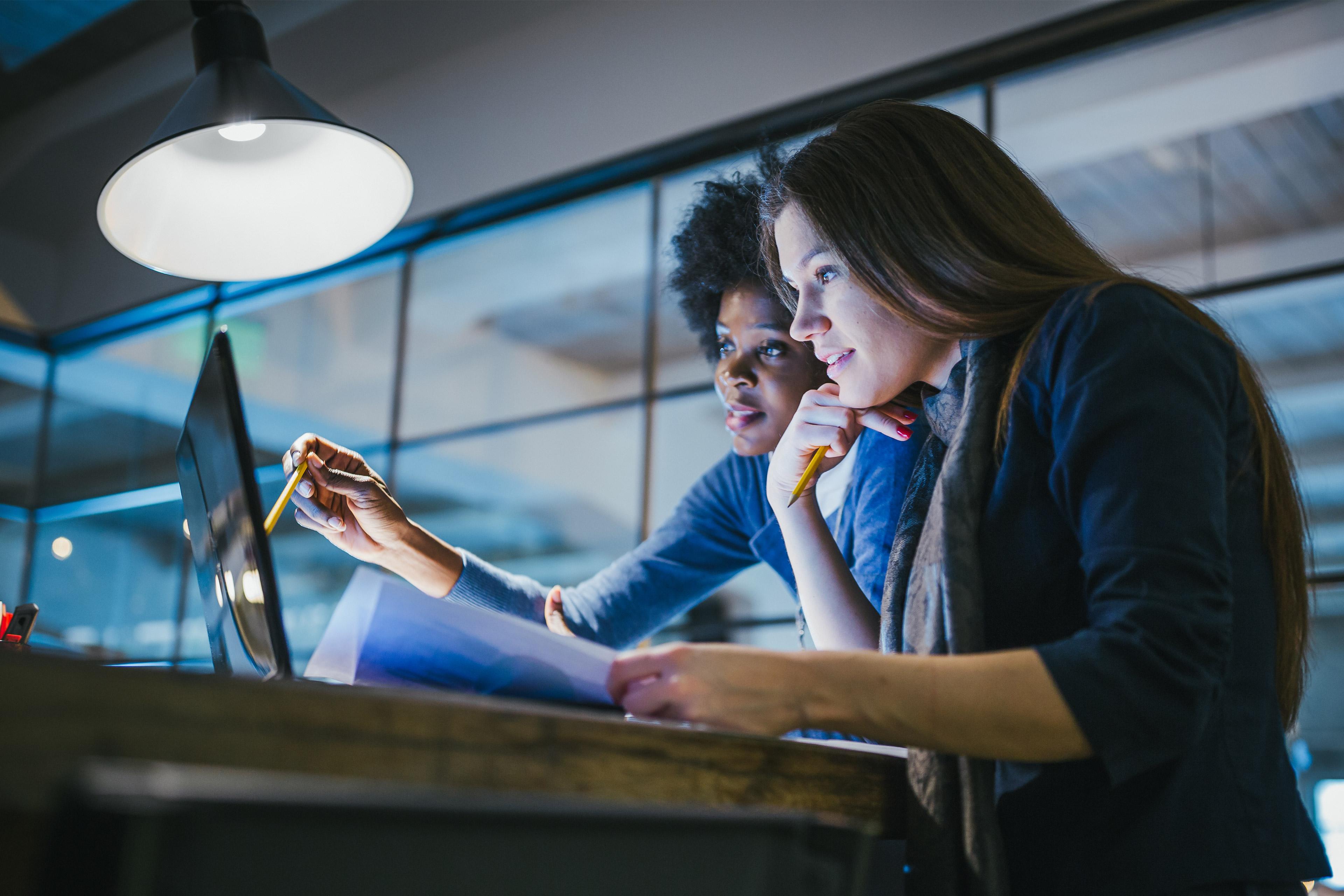 Digital-Karriere bei EY im Bereich Technologie- und SAP-Beratung: Zwei junge Frauen prüfen Einträge auf einem Laptop.