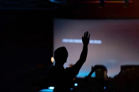 Man raising hand to vote.