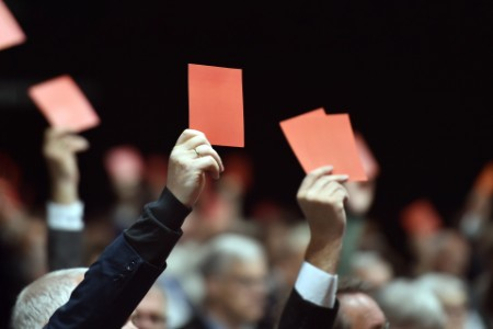 men voting with red cards