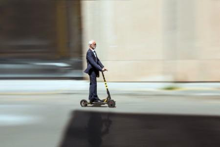 Geschäftsmann auf einem E-Scooter in der Stadt - Elektromobilität