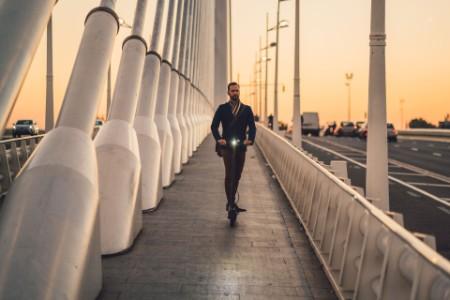 Junger Mann fährt mit E-Scooter über Brücke