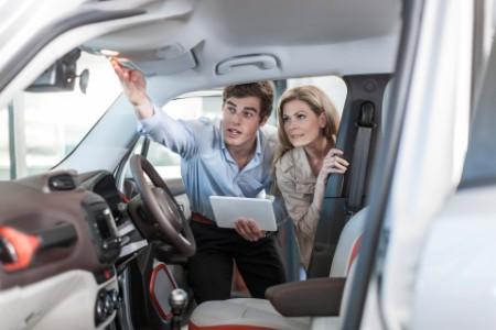 Verkäufer zeigt einem Kunden ein neues Auto