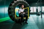 Mann sitzt auf Reifen mit Laptop