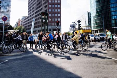 Personen auf Fahrrädern überqueren eine Straße