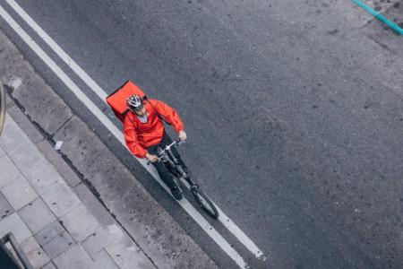 Ein Zusteller, der ein Fahrrad fährt