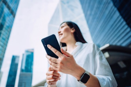 Low angle view of confidence and successful young Asian businesswoman using smartphone on the go in financial district, against corporate skyscrapers during the day in the city