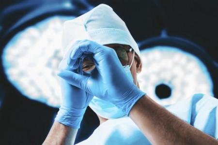 Porträt eines Arztes auf dem Hintergrund der chirurgischen Lampen. Medizin Konzept.