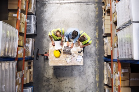Vue en plongée d'un superviseur utilisant un ordinateur portable avec des travailleurs.