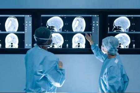 Chirurgen, die während der Operation auf MRT-Scans schauen