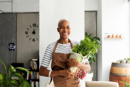 Frau in Schürze trägt frisches Gemüse in einem Netzbeutel