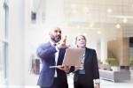 Ein Geschäftsmann zeigt einer Geschäftsfrau einen Entwurf des Geschäftsplans