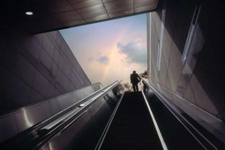 Mann fährt eine Rolltreppe hinauf
