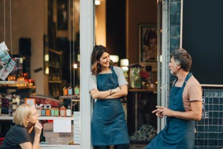 Drei Personen stehen vor dem Laden.