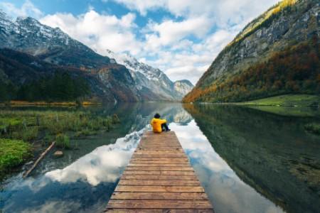 Mann sitzt auf einem Steg am Wasser