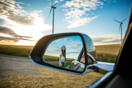 Reflexion einer Dame im Rückspiegel in einem Windfeld