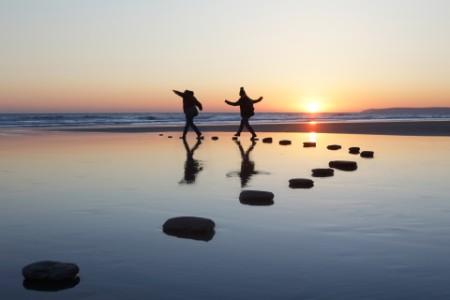 Zwei Menschen springen auf Stein im Wasser