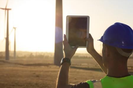 Arbeiter fotografiert mit seinem Tablet einen Windpark