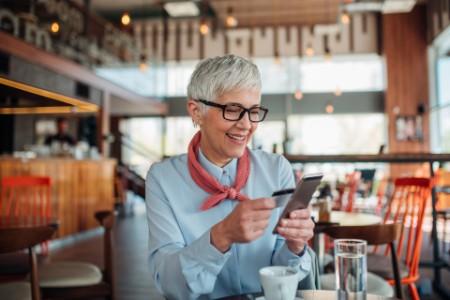 Frau benutzt Smartphone und Kreditkarte zum Online-Shopping