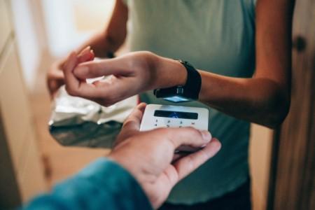 Frau zahlt kontaktlos mit Smartwatch