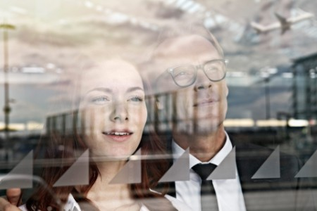 Frau und Mann blicken durch Fensterscheibe