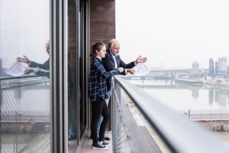 Geschaeftsmann und junge frau sprechen auf dem Balkon
