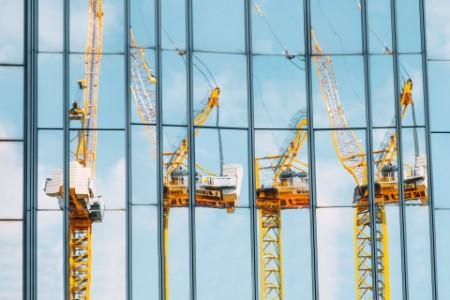 Kräne spiegeln sich in Glasfassade