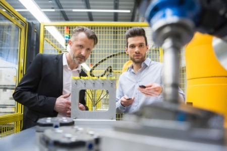 Geschäftsmänner mit Roboter in der industriellen Produktion
